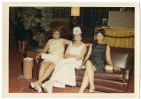 Photo of three ladies on brown couch.