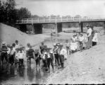 Group of dressed-up boys wading in the river