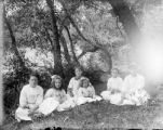 Six girls seated in a wilderness area