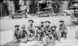 Military men on sidewalk in WWI uniforms posing with machine guns