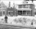 Man in front of three snow-covered buildings on S. Broadway
