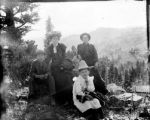 Family seated in mountain setting