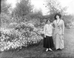 Two women standing arm in arm by flower beds