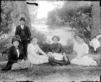 Group of adults and a baby seated by the river