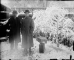 Two men in overcoats with suitcases standing by the Alameda Avenue bridge with snow