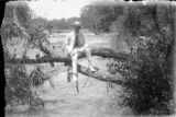 Man seated on tree limb extending over river