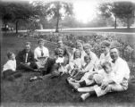 Family group seated on the grass in a park