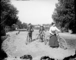 Man woman and girl with bicycles woman carries a rifle