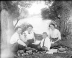 Man two women and a boy sitting on a blanket by the river reading