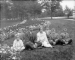 Family seated on grass in park