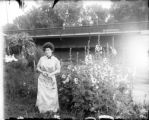 Woman standing near a bunch of morning glories by the Alameda Avenue bridge
