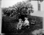 Small boy and girl with a toy wagon filled with flowers