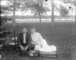 Couple seated in park with their hats on the grass in front of them