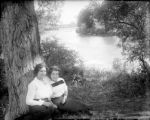 Two young women seated by the river