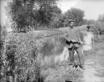 Young man with rifle standing near the canal small dog at his feet