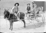 Three men on wagon beside R. W. Ostrom & Co. Bldg