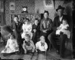 Group photo of family (man, woman, seven children) interior of house