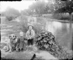 Two children and dog beside stream