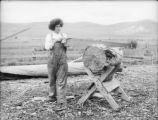 Agriculture - ranching - woman sawing a log