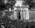 Five young women standing in a line with hands on each other's shoulders (City Park?)