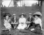 Five adults and a child seated on the grass in a park