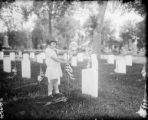 Young girl putting flag on grave, Armistice Day