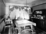 Interior of stone residence of Wilbur S. Raymond showing one end of dining room