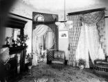 Interior of stone residence of Wilbur S. Raymond showing one corner of parlor