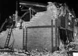 Firemen probe the crumbled walls of the Paris Theater, 76 Knox Court