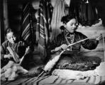Navajo girls carding and spinning wool for rugs