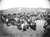 Beef distribution, Dakota, groups of people standing in and around a wooden fence, church and...