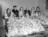 Telephone Co. girls give dolls to firemen for 1940 Christmas