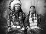 Good Horse, Dakota Chief, with wife, seated, Good Horse in elaborate Indian clothing, with...
