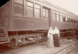 Women beside passenger cars
