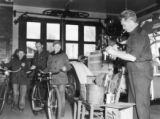 Fireman putting Scotch lite tape on bicycles @ 1540 E. Virginia Ave., Fire Station no. 21