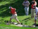 Bubba Watson (left) and his caddie cross over a small stream on the 17th fairway after Watson had...
