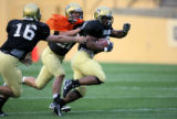 (L-R) Mason Crosby (#16) and Scotty McKnight chase after Brian White as he carries the ball at a...