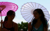 (l-r) Katrina Han, 17, and Christine Vongphackdy, 17, both of Westminster keep in the shade of...