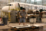 Gus Kunz, mechanic for Frontier Airlines, pressure washes interior panels of a Airbus that is...