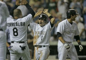 Colorado Rockies' player Jamey Carroll gets high fives from teammate Yorvit Torrealba as he cheers...