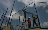 Jeff Gradolf, on a ladder, Eugenio Guillen, holding, and Sergio Aceves put up a fence around the...