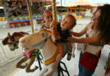 MJM109 Having their choice of rides on an uncrowded midway, Nong Yang (cq),left, holds his son,...