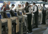 Travelers use the United Airlines automated ticket machines at DIA Thursday afternoon May 11,...