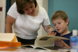 Principal Joanna Martinez listens as third-grader David Ibanez reads at Colfax Elementary in...