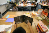 "Fourth-grader Alejandro Mata, center, reads the ""The Spider and the Fly"" in Tracy..."