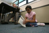 Third-grader G' Anna Matsunaga reads on the floor next to teacher Tracy Booker at Colfax...