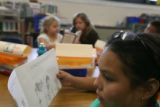 Third-grader Angelica Nu–ez, foreground, reads as teacher Tracy Booker helps third-grader Haley...