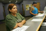 Simona Perez (cq), left, of Denver, checks in at the front desk at the Westside Workforce Center...