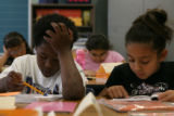 Third-graders Jerome Johnson, left, and Brianna Rivera read during class at Colfax Elementary in...