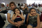 (L-R) Maria Santos Soto (mother),  holds her daughter Jacquelin,2, and Eileen,4, as they have...